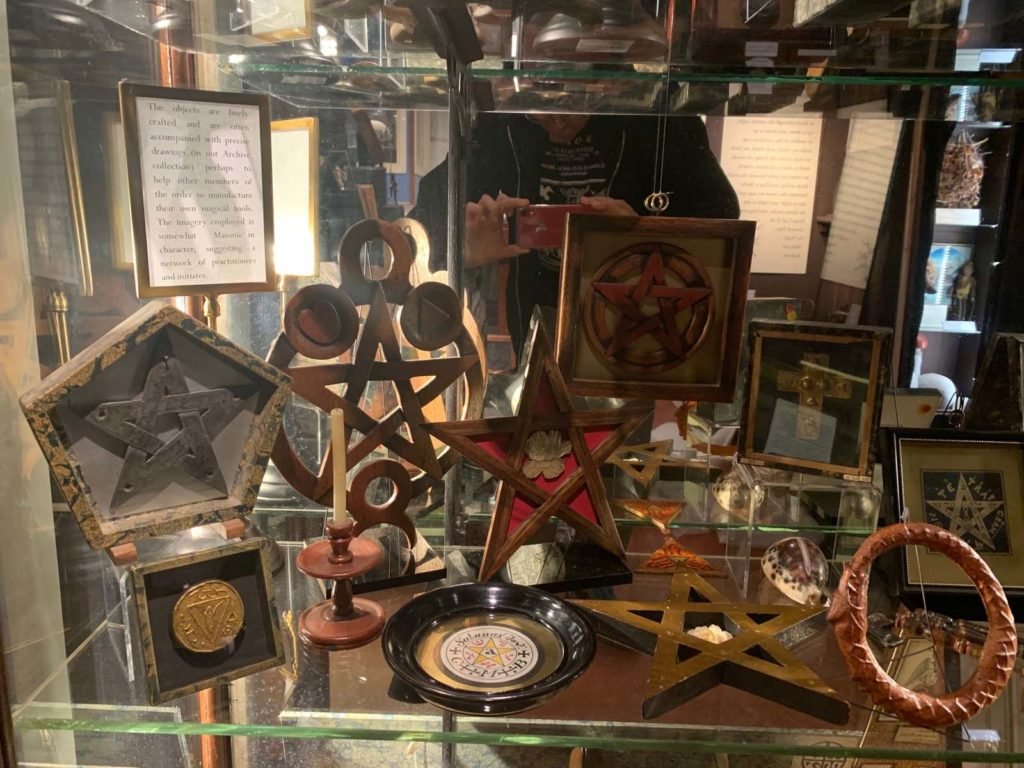 A museum display case showing a variety of different pentagrams