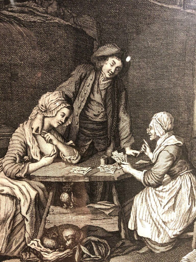 print showing man stood and woman seated at a table, having their fortune told by a woman sat opposite them