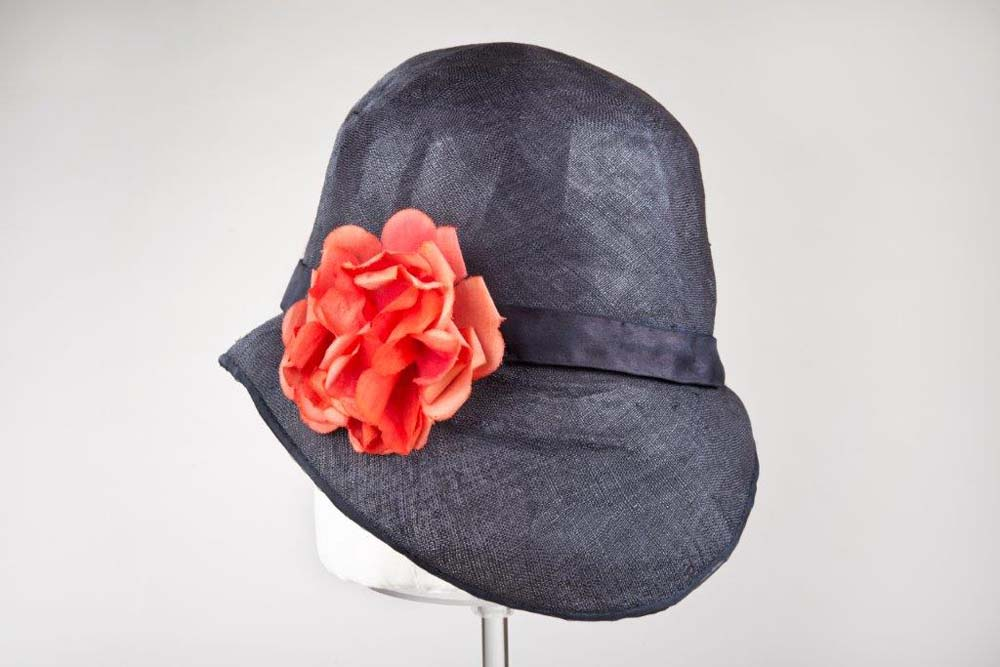 a 1920s style hat with a large red flower on the side