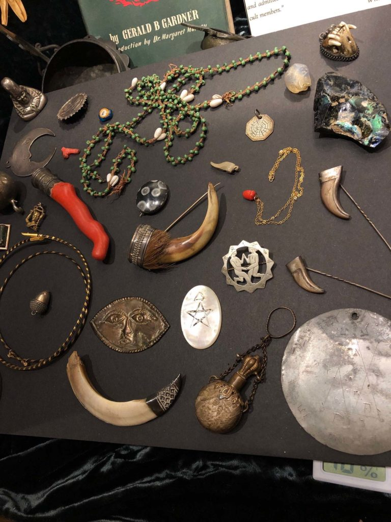 a table covered in a variety of different charms, amulets and talismans, many made from horn