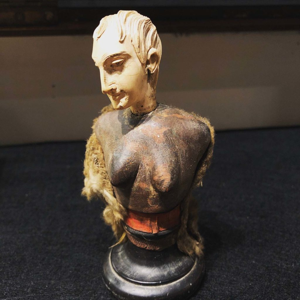 an object consisting of a man's head carved from bone atop a women's torso carved from wood on a stand