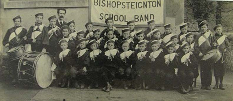 a photo of a large grop of boys in uniform and hats in a band