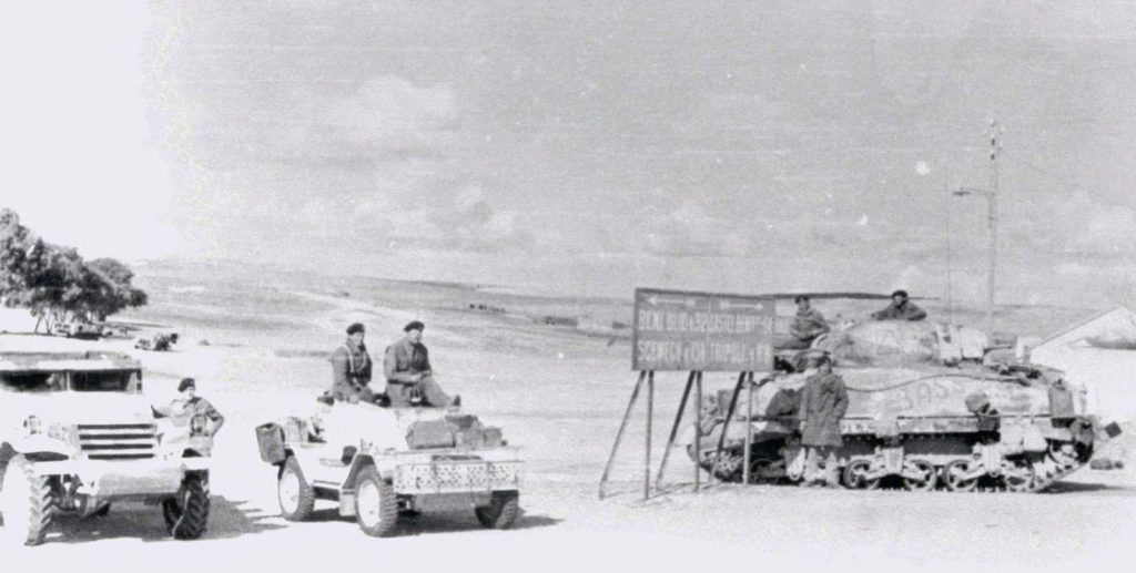 a black and white photo of soldiers with aroured cars and a tank in the western desert during World War Two