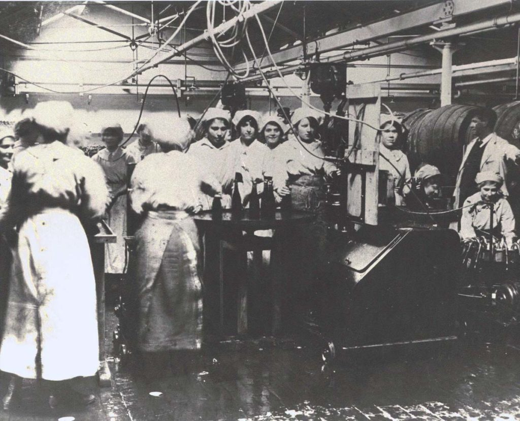 a black and white photo of a crowded factory filled with women filling bottles of beer