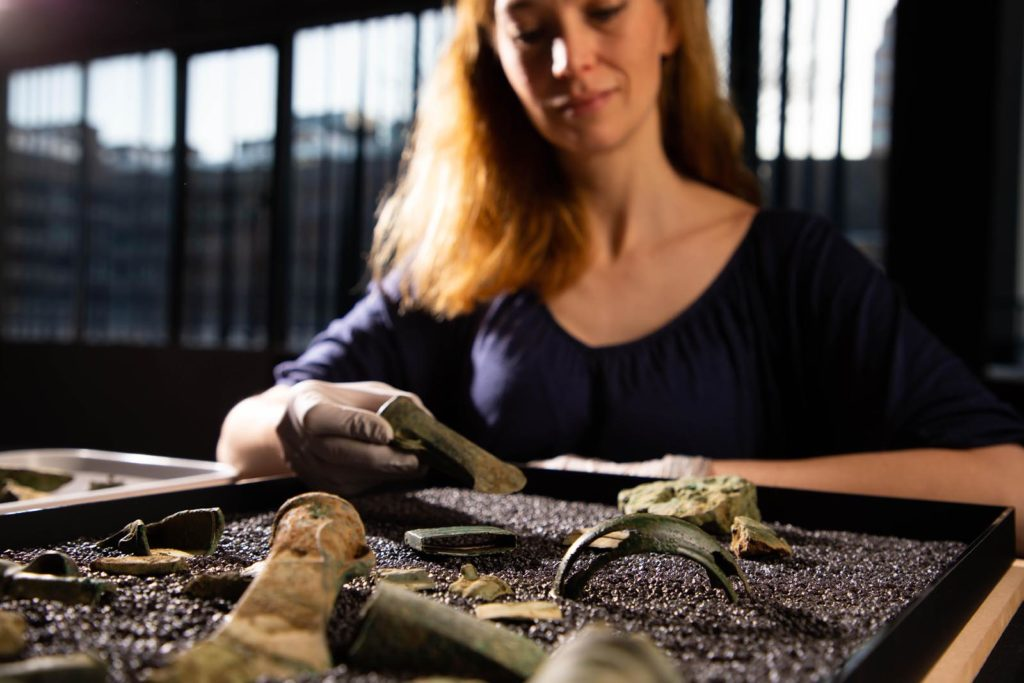 a photo of a woman with a tray of archaeological objects