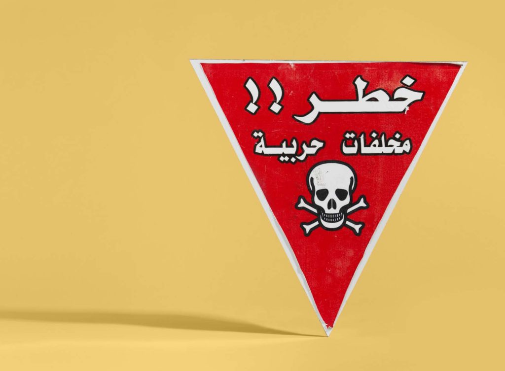 photo of a red triangle bomb warning sign with skull and cross bones together with Arabic writing