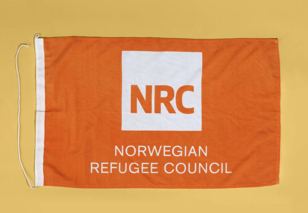 orange flag with white NRC logo and Norwegian Refugee Council in white writing