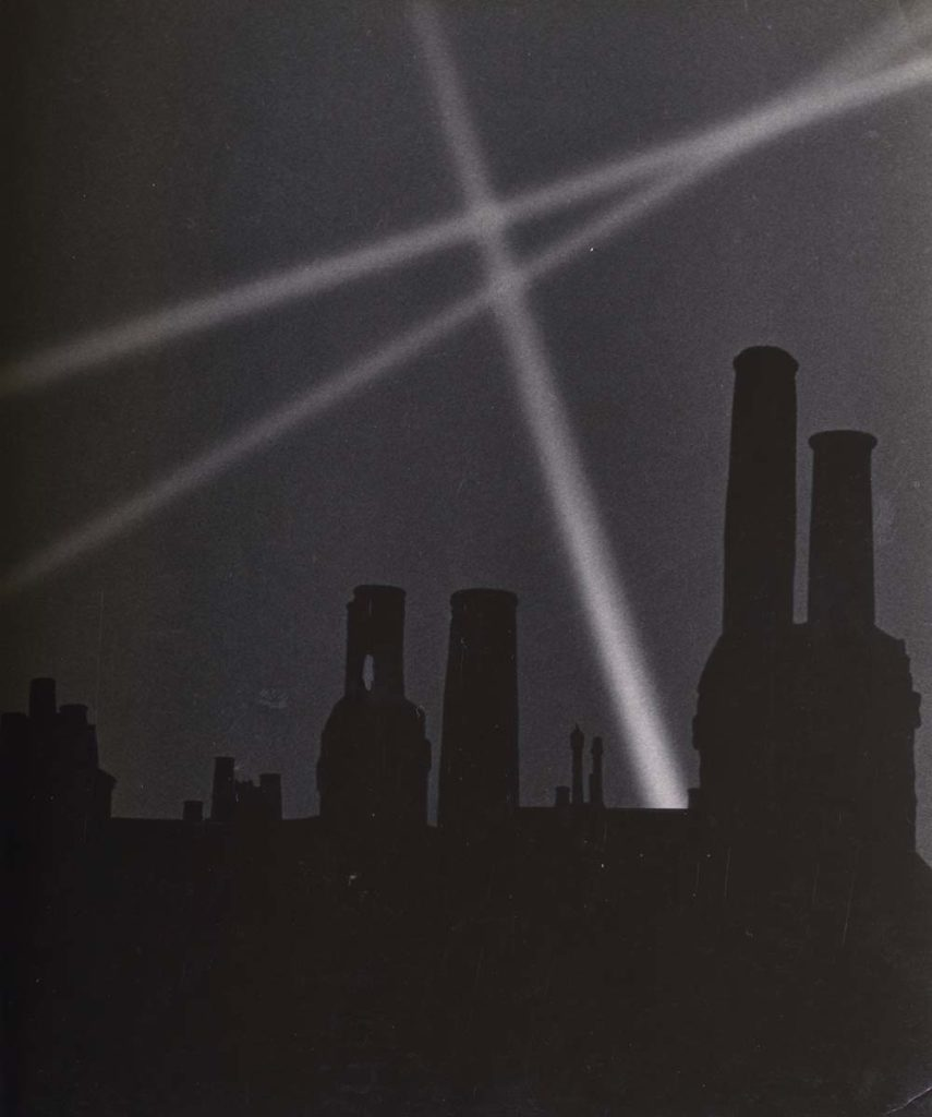 a photo of searchlights beaming into the sky