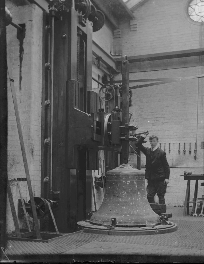 photo of a man next to a large bell with a lathing bore coming down into its top