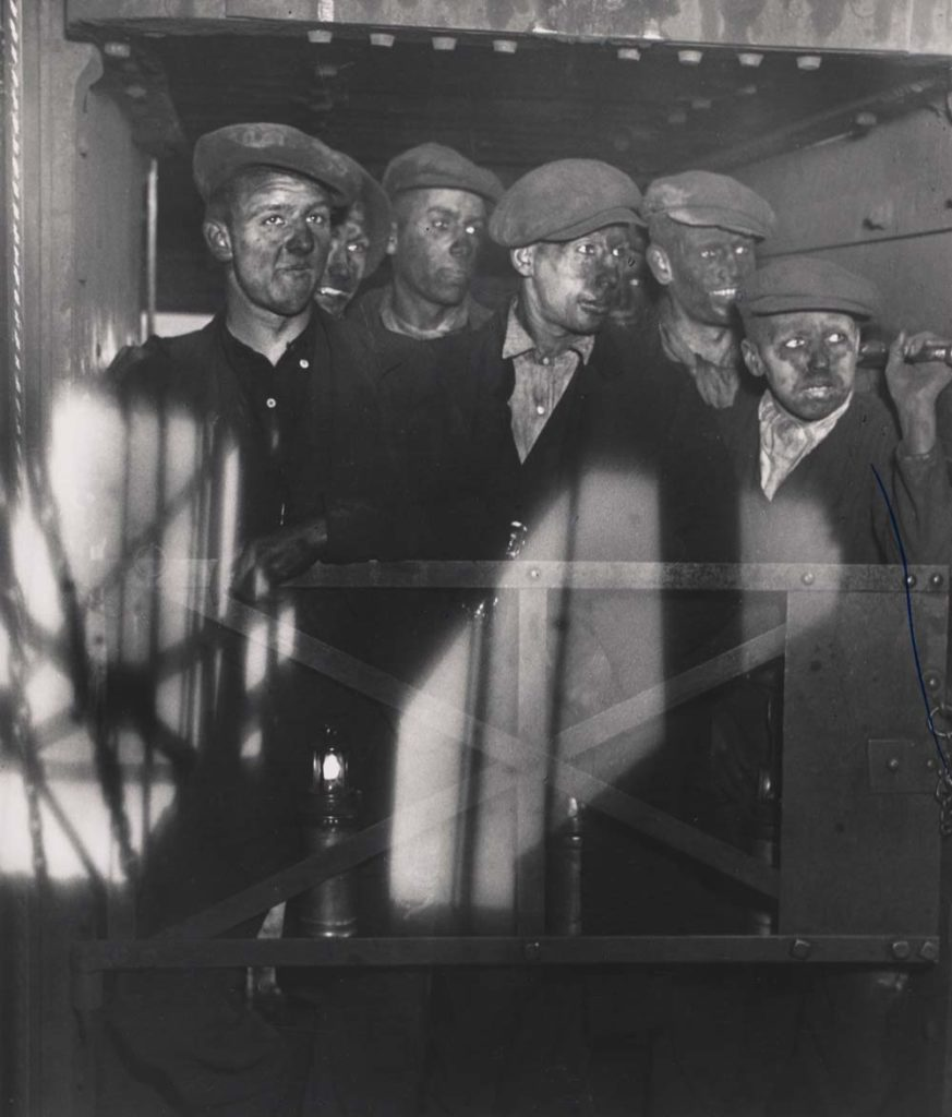 a photo of a group of miners in a lift cage