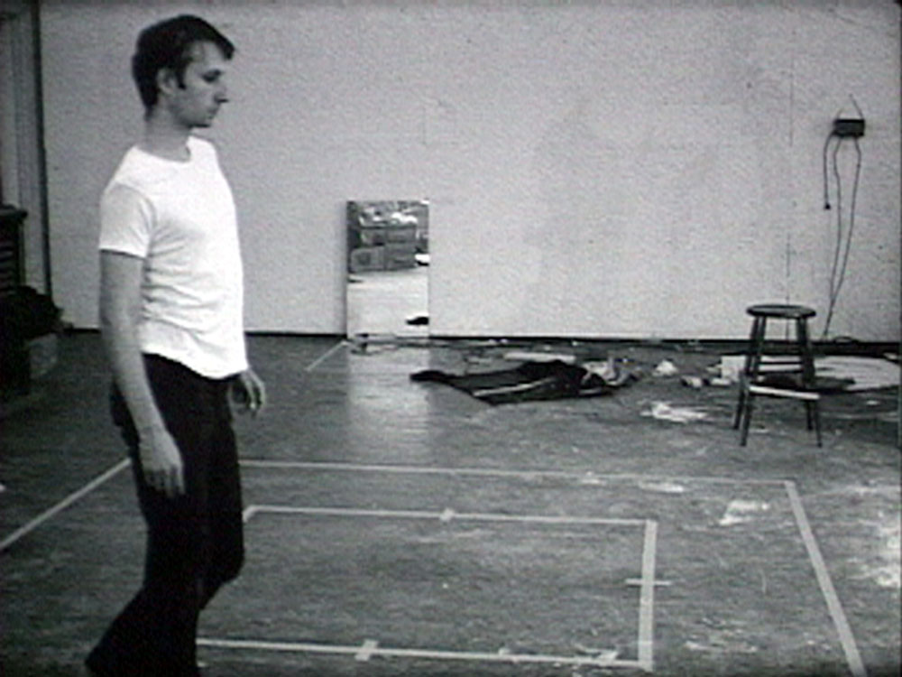still from black and white video artwork showing man walking along a square marked out in tape on the ground