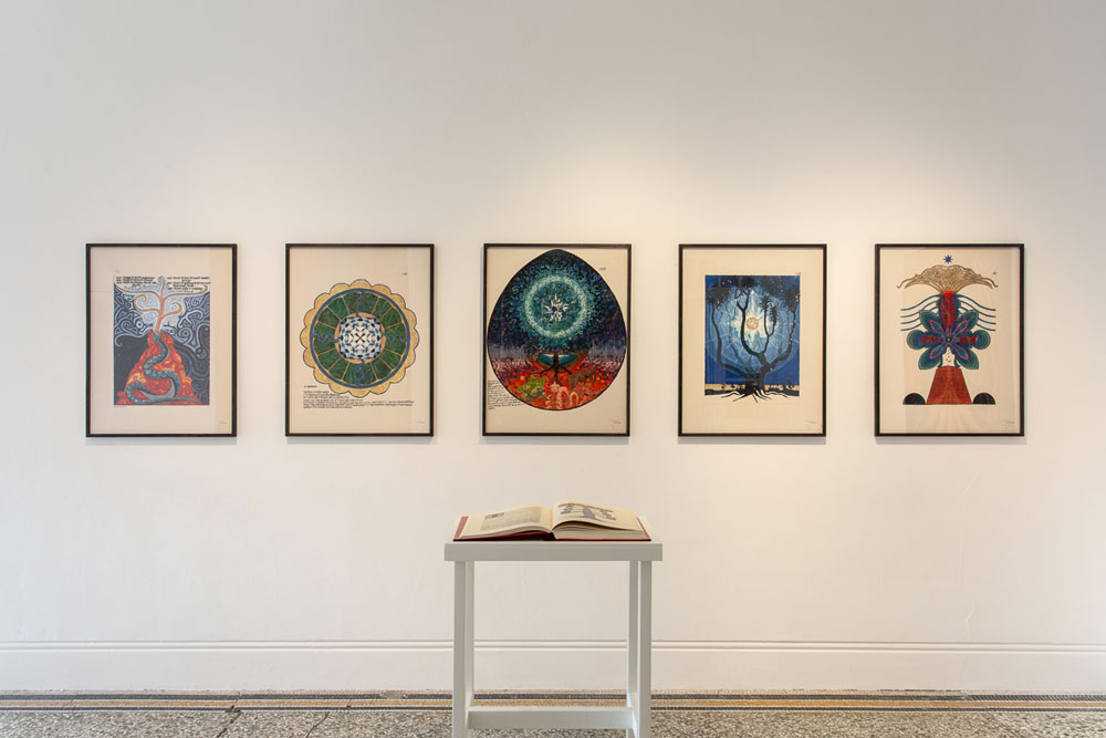 installation view of The Botanical Mind exhibition showing five artworks on a wall with an open book in front