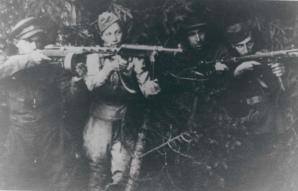 photo of partisan soldiers firing weapons in a forest