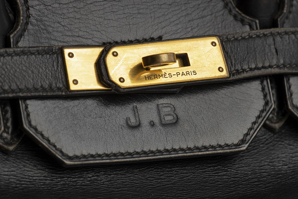 close up of clasp on black Hermes bag, with J.B stamped into the leather