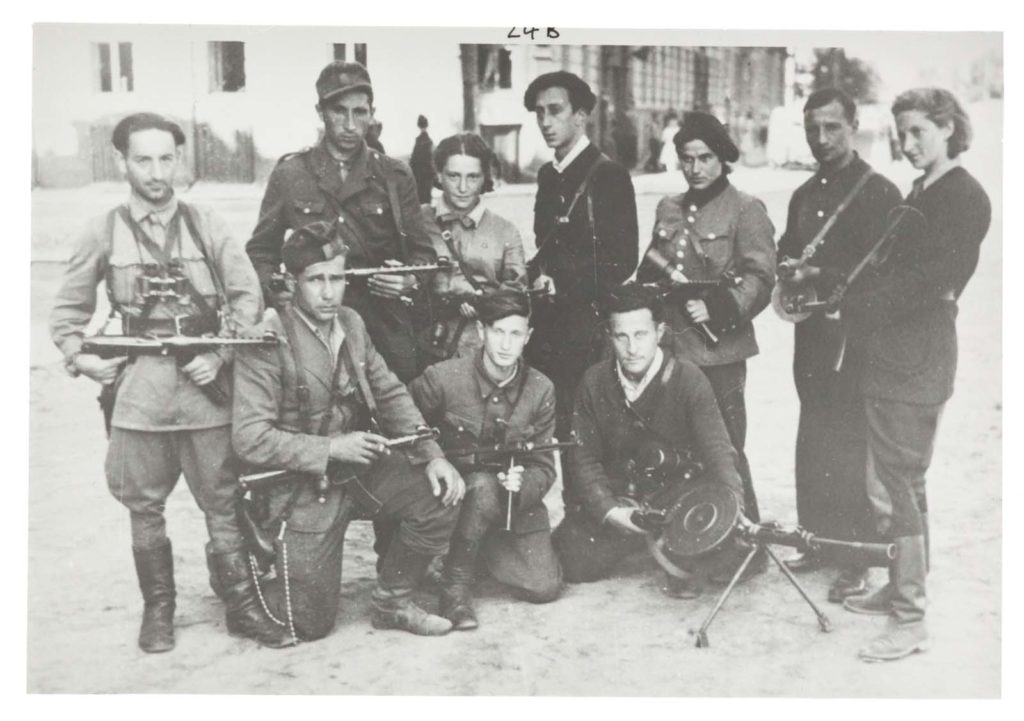 a black and white photo of male and female fighters posing in a group with their guns