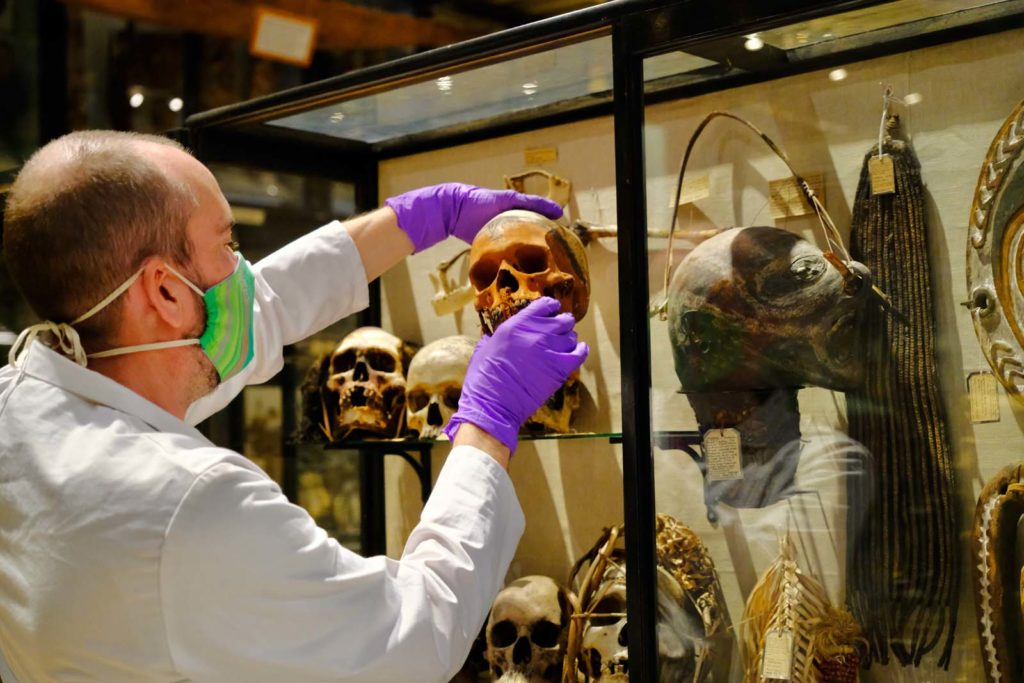 photo of a man in a lab coat removing a human skull from a case