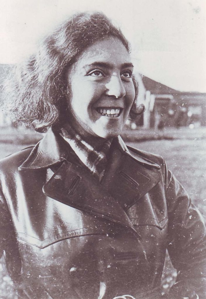 a photo of a smiling yung woman in a leather coat