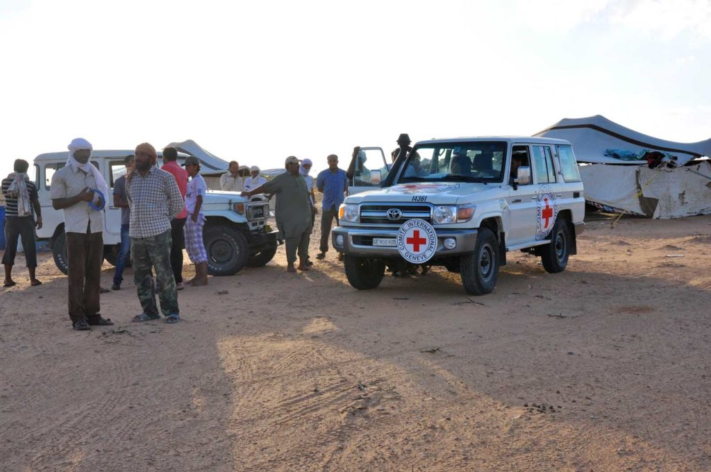 photo of two white aid vehicles in an aid camp