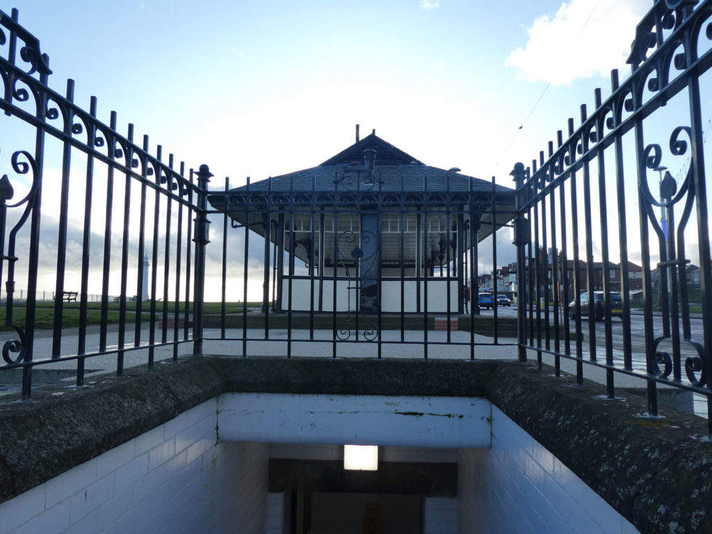 entrance to underground public toilets, showing ornate wrought iron fencing