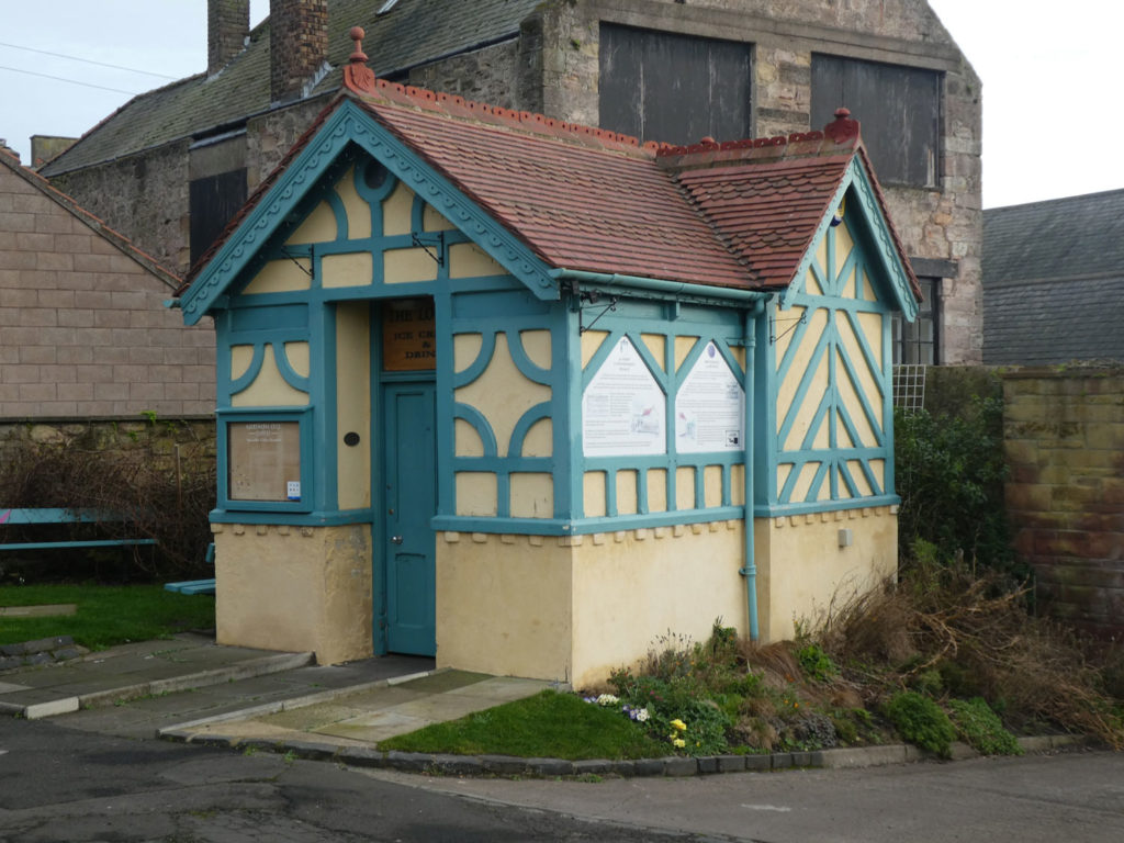 exterior of small toilet block building with cream walls and blue decorative wood panelling