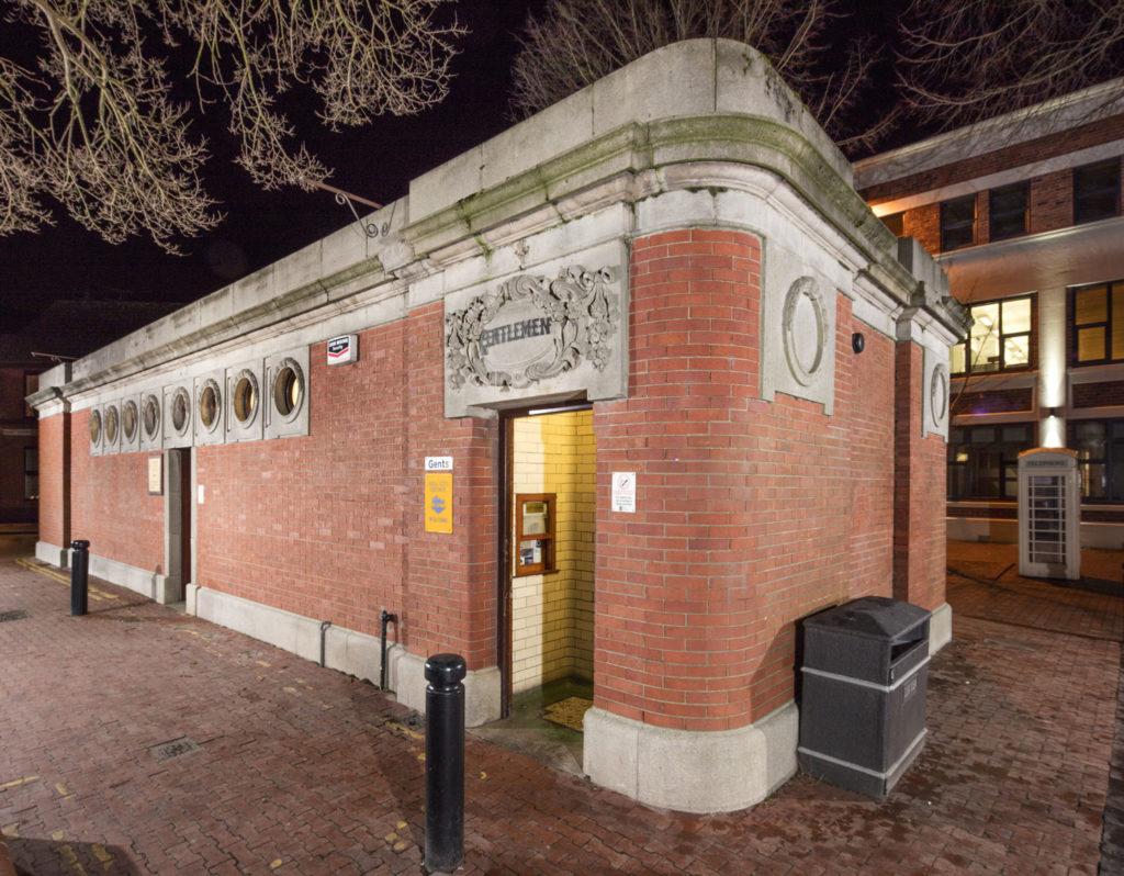 brick public toilet building showing entrance with decorative 'gentlemen' sign