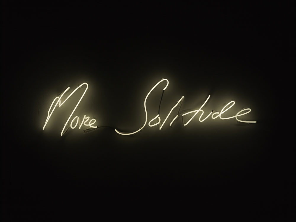 pale yellow neon light reading 'more solitude' on black background
