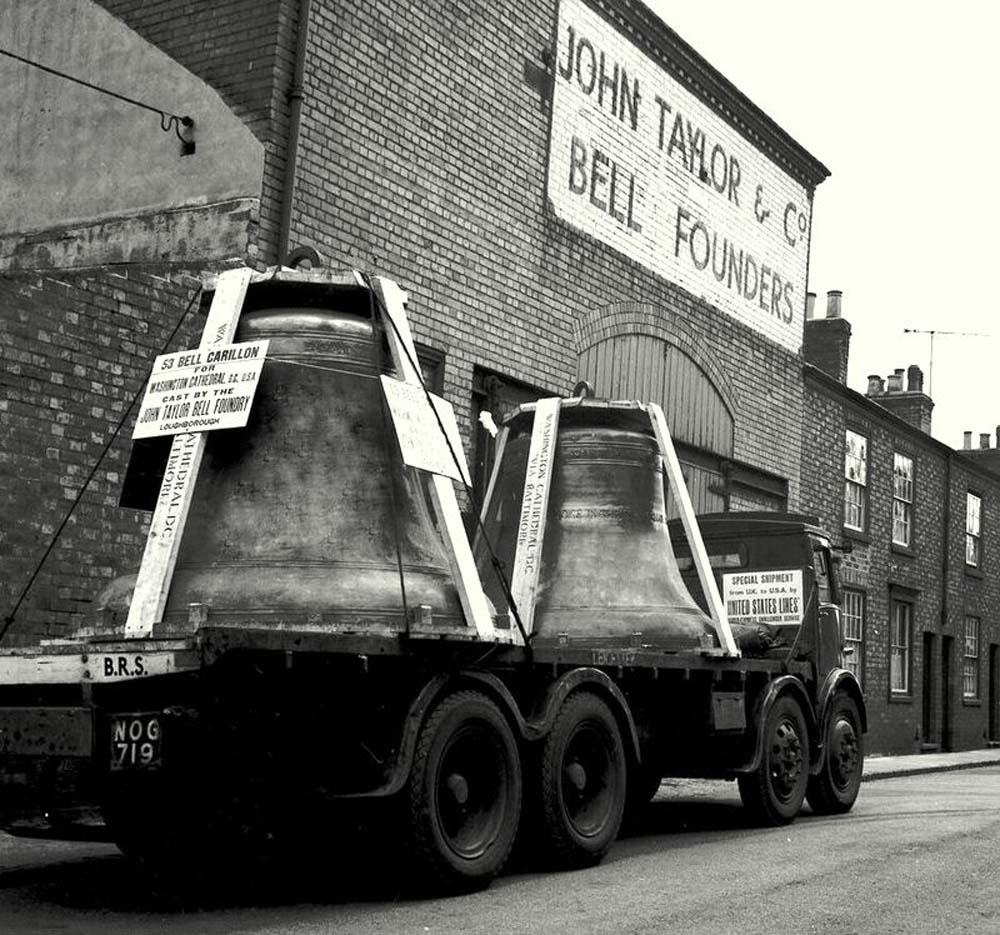 a black and white photo of two very large bells on the back of flatbed truck