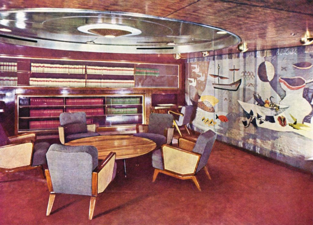 photo of an interior with round table, chairs, bookcase and wall tapestry