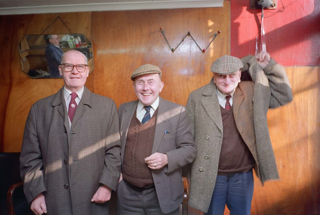 photo of three men in jackets coats and flat caps in a working men's club or pub