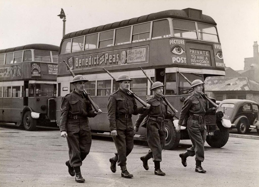 photo of four soldiers marching past parked double decker buses