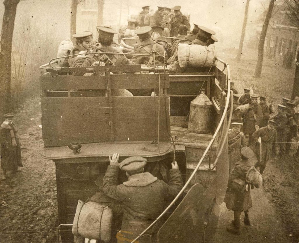 black and white photo of WWI soldiers crowded onto a double decker bus
