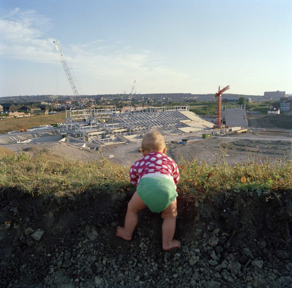 colour photo of a baby peering over bank towards an industrial landscape