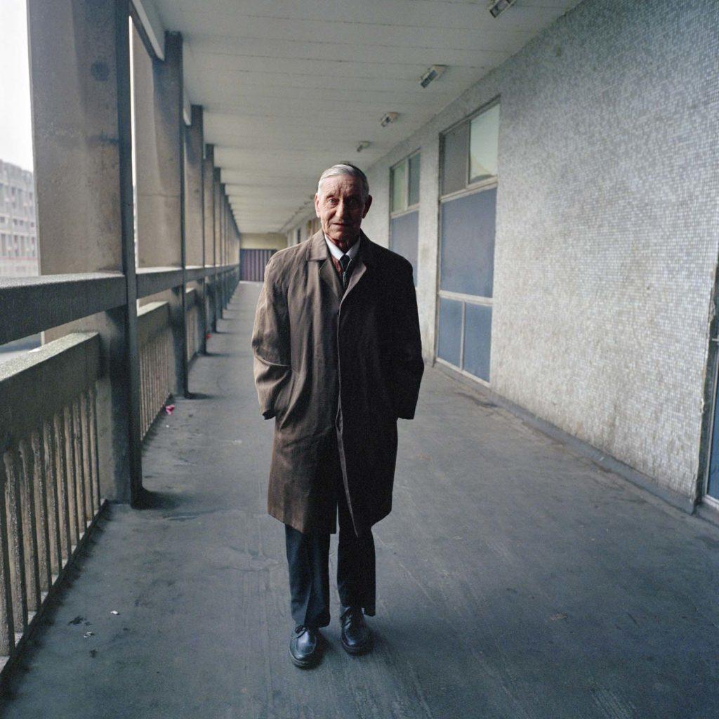 photo of an elderyl man in overcoat walking down a walkway of a block of high rise flats