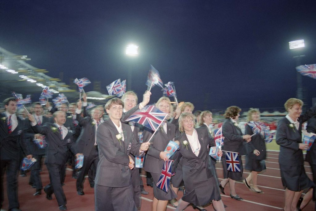 a photo of a group of people waving union jacks whilst walking round a track wearing blue suits