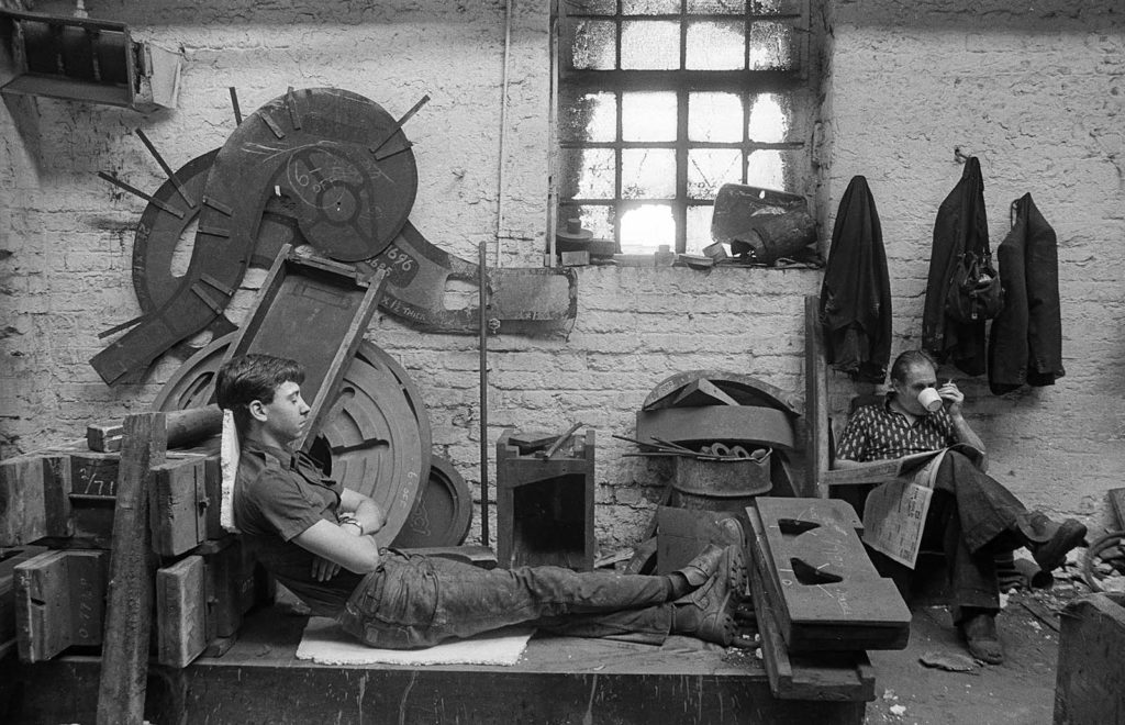 black and white photo of a man resting on a bench in a steel works