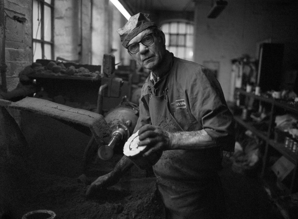 black and white photo of a working man in a workshop