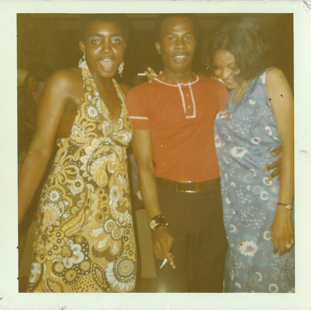 group photo of a man and two women in floral dresses at a party