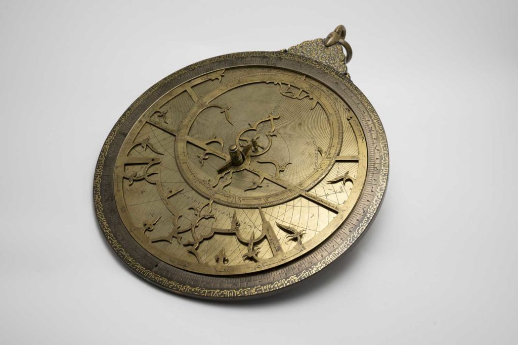 photo of an ornate round face of an astrolabe - a clock like device with hands