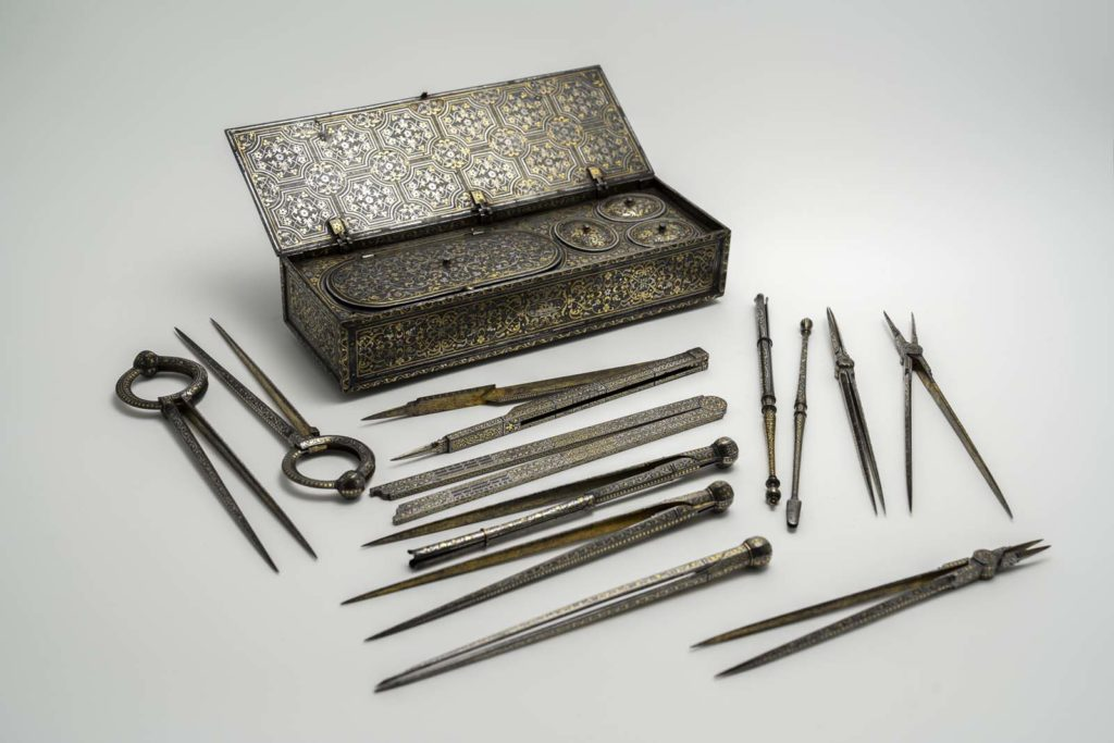 a photo of a metal engraved box wiht drawing instruments laid out before it