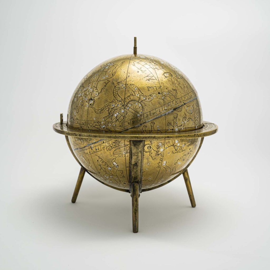 a photo of an engraved metal globe in a stand
