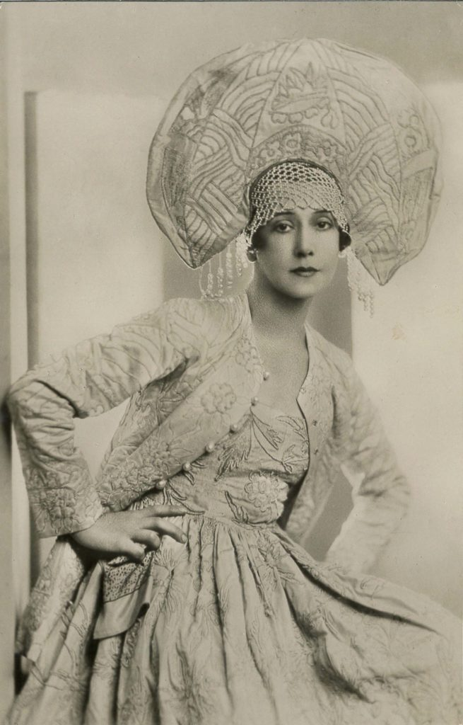 black and white studio portrait of a woman with a dance costume including a fan plumed hat