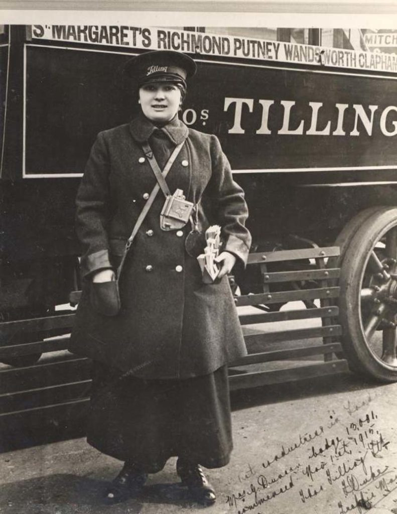 photo of a woman bus conductor next to her bus