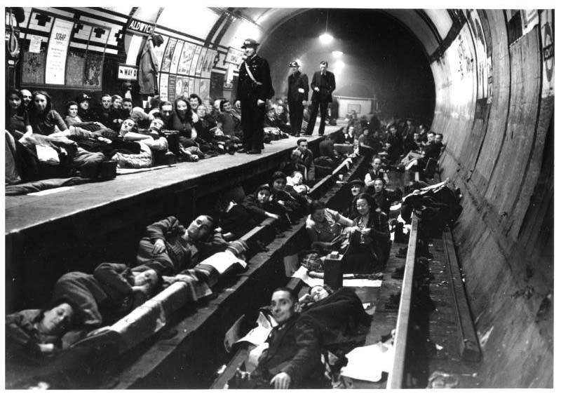 Black and white image of a group of people sheltering at Aldwych Station. People are sleeping on both the tracks and the station platform.