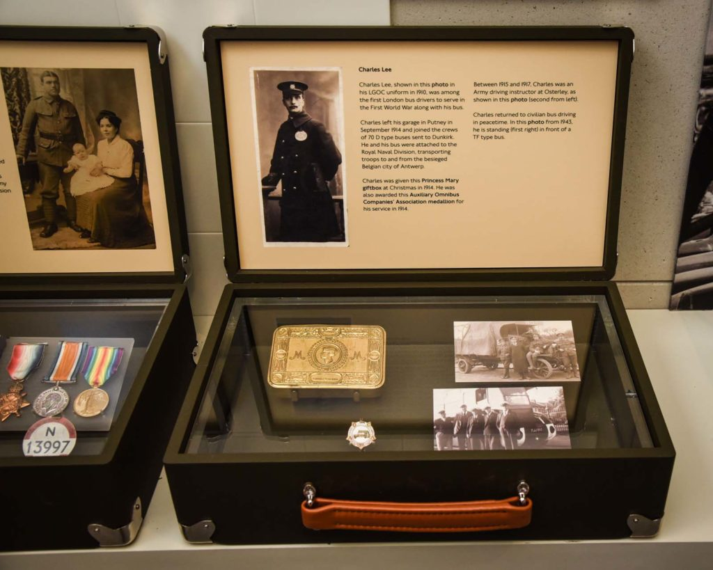 a museum display case with a Princess Mary tin, medal and photographs of veteran bus driver