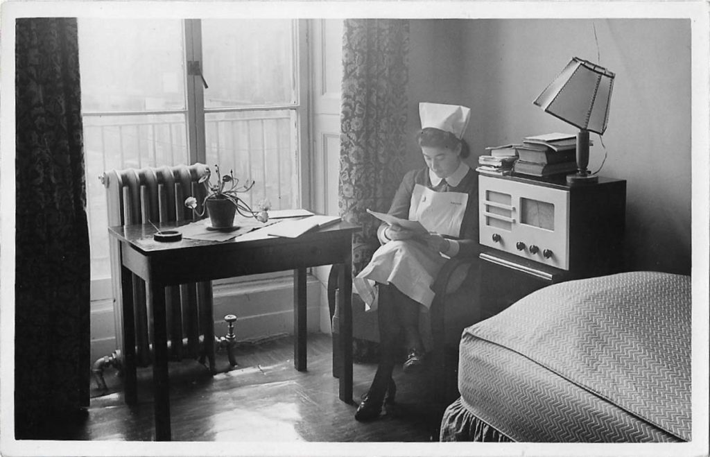 black and white photo of a nurse sitting in the corner of a room reading a magazine