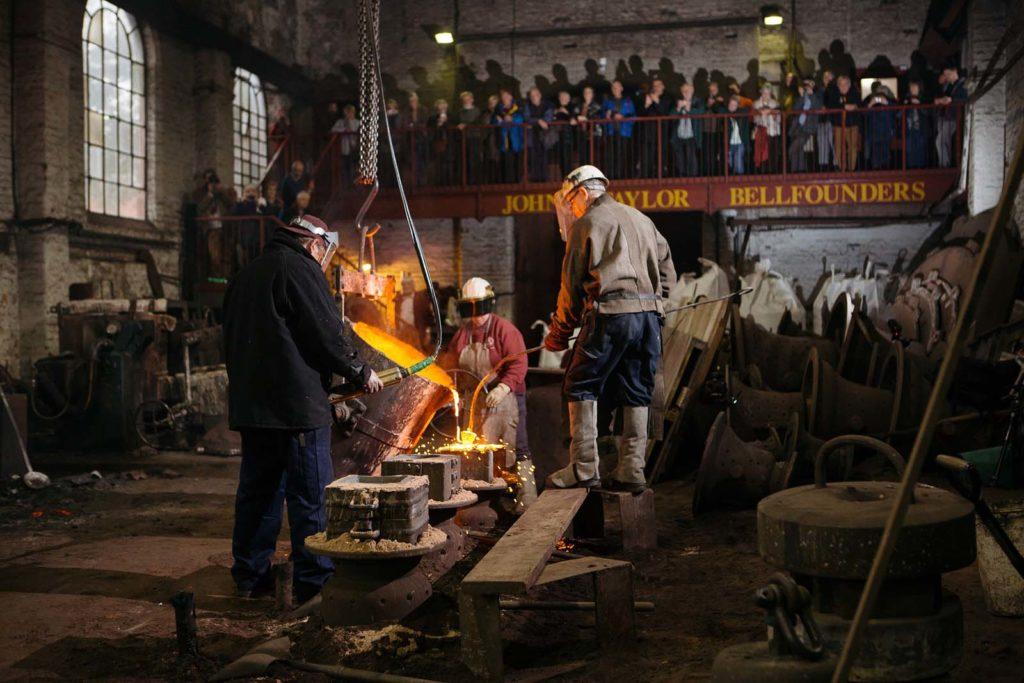 photo of men pouring molten bronze into castings