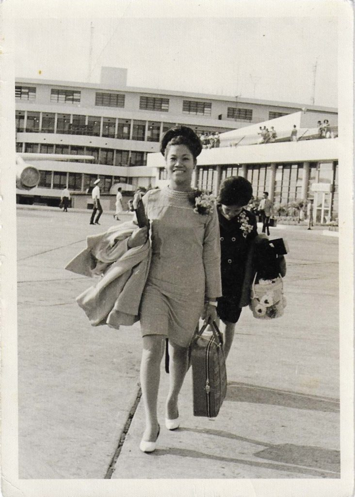 photo of a young woman with a suitcase walking across an airport tarmac