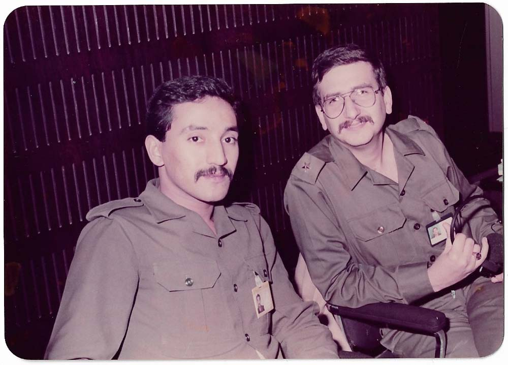 a photo of a two seated Iraqi men with moustaches and khaki military uniform