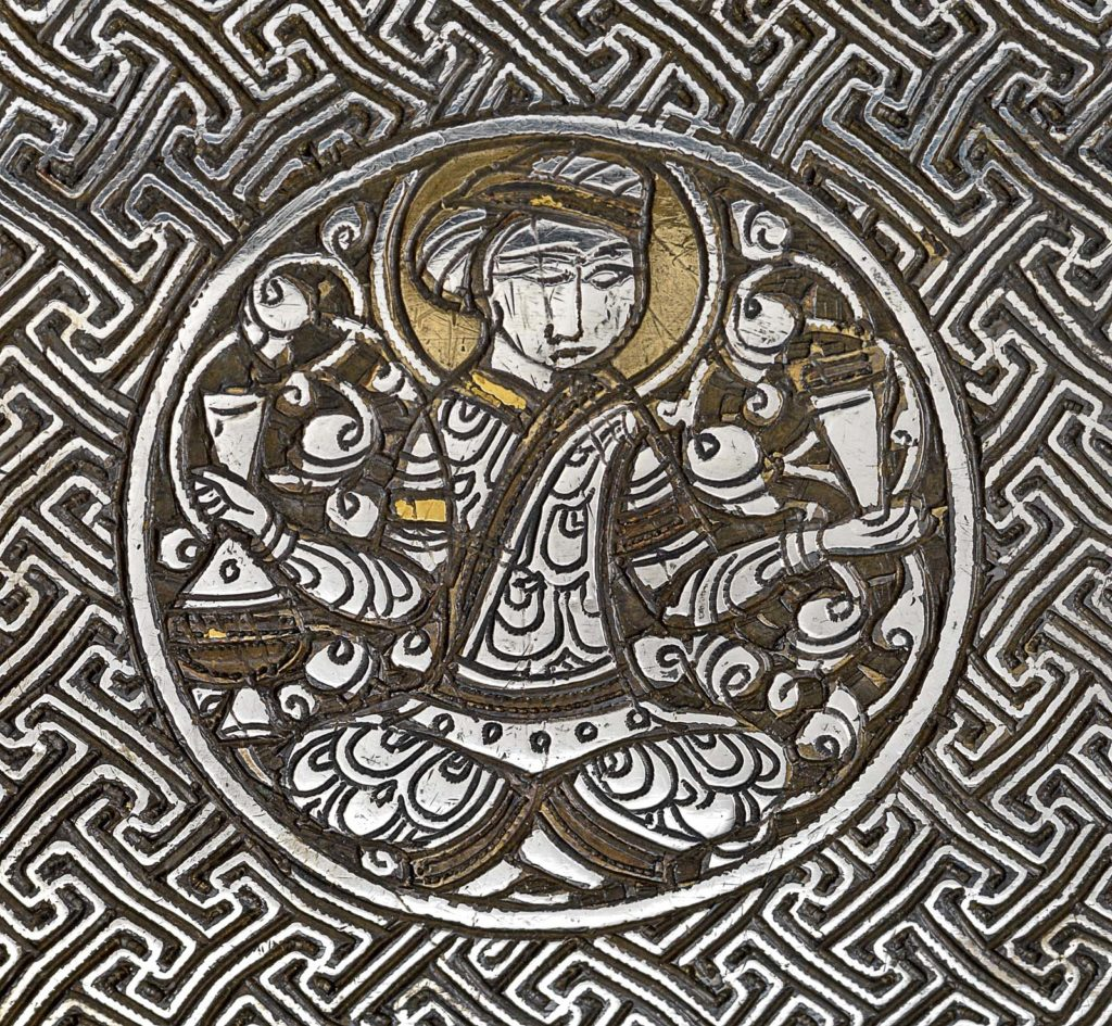 detail of brass and inlaid silver engraving of a figure