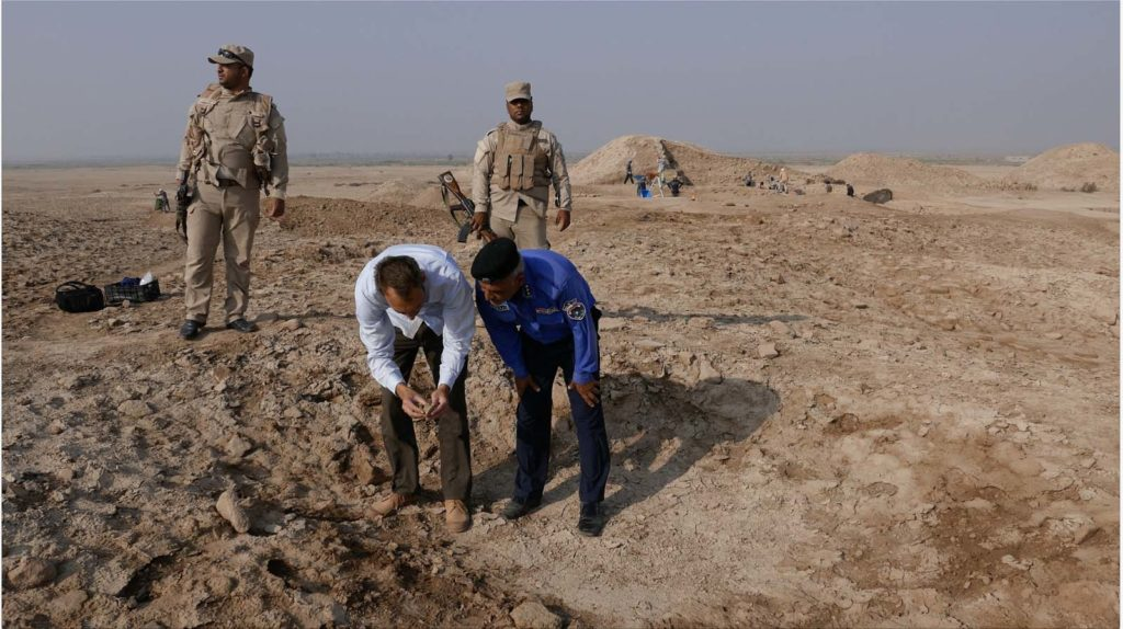 a photo of two men in a desert setting looking at something as two armed soldiers watch them
